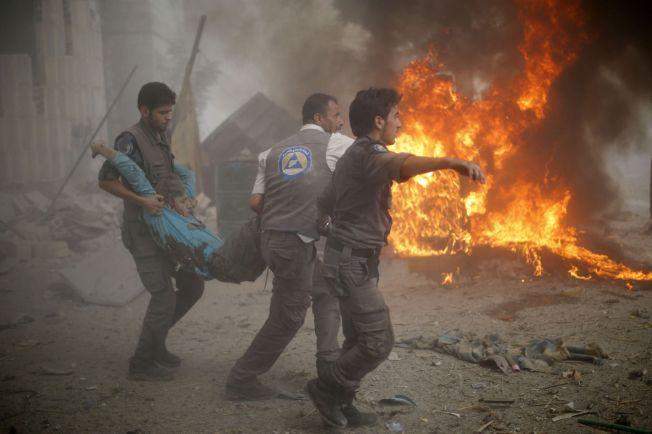 DREPES AV REGIMET: Innbyggere i Douma forsøker å hjelpe en skadet mann etter at Assad-regimet bombet Douma øst for Damaskus i slutten av august. Assads massedrap på sivile har fortsatt med full styrke gjennom året.