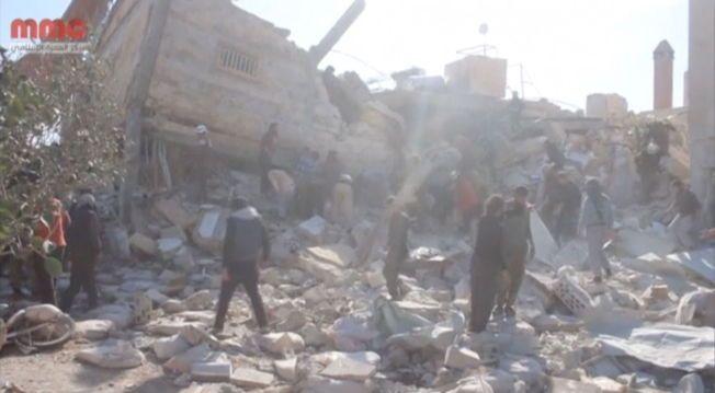 I GRUS: Folk samler seg ved en ødelagt bygning som skal vise Leger Uten Grenser -sykehuset i Marat al Numan som ble truffet av bombet mandag.