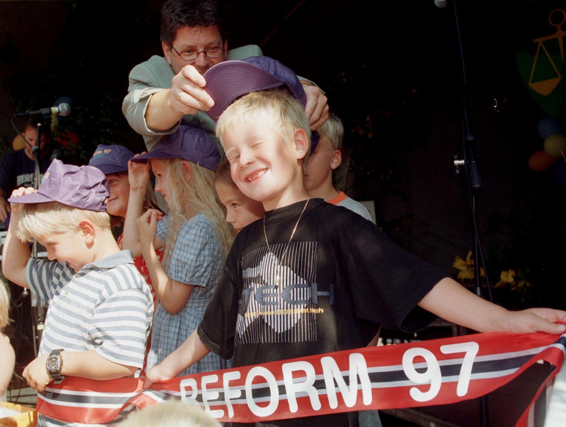 STARTET SOM SEKSÅRINGER: Daværende utdanningsminister Reidar Sandal (Ap) setter capsen på hodet på en av de første elevene som begynte på skolen som seksåringer – foran Eidsvollbygningen 13. august 1997.