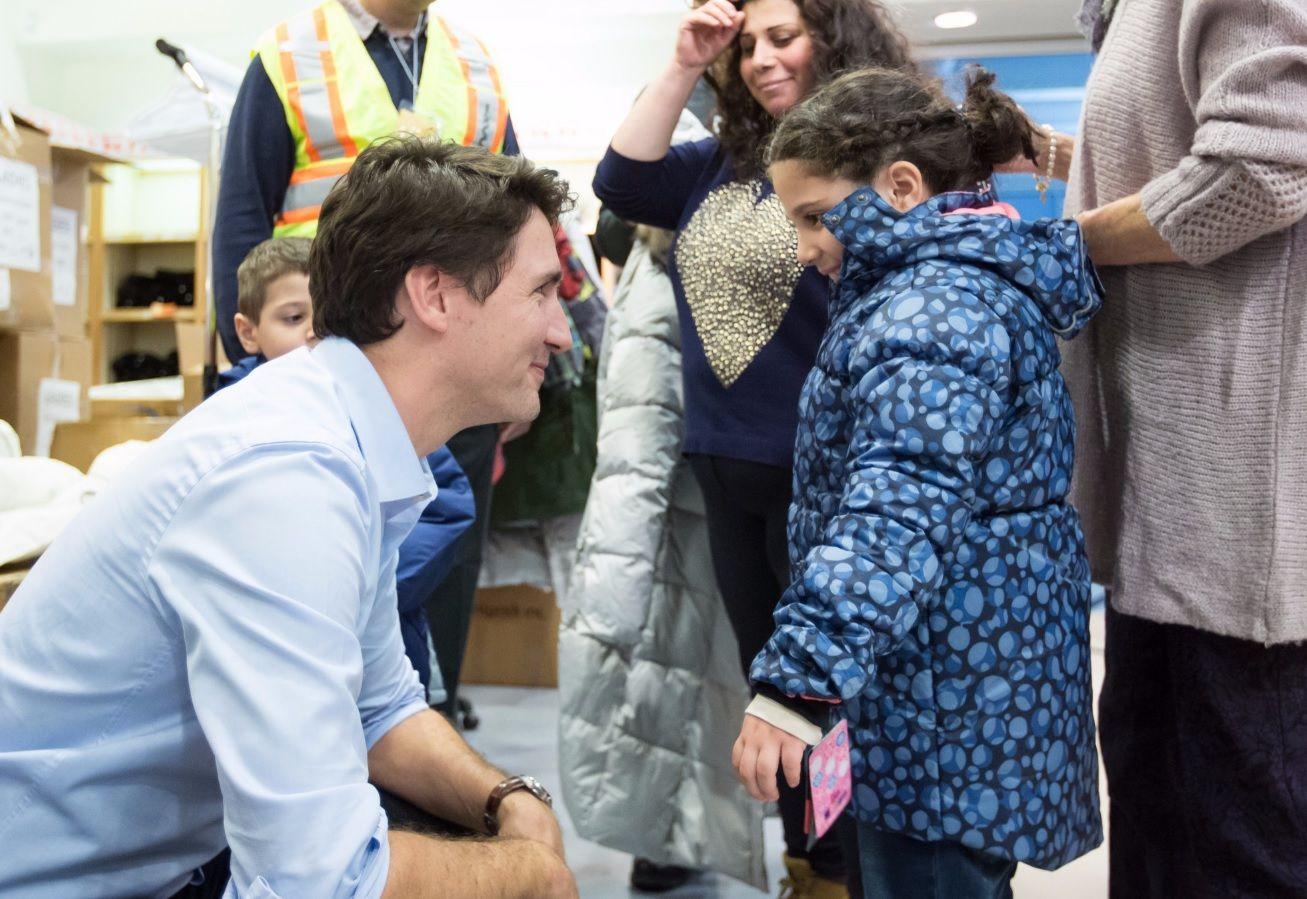 ÅPNE ARMER: Canadas statsminister Justin Trudeau tar her i mot en syrisk jente på flyplassen i Toronto i 2015.