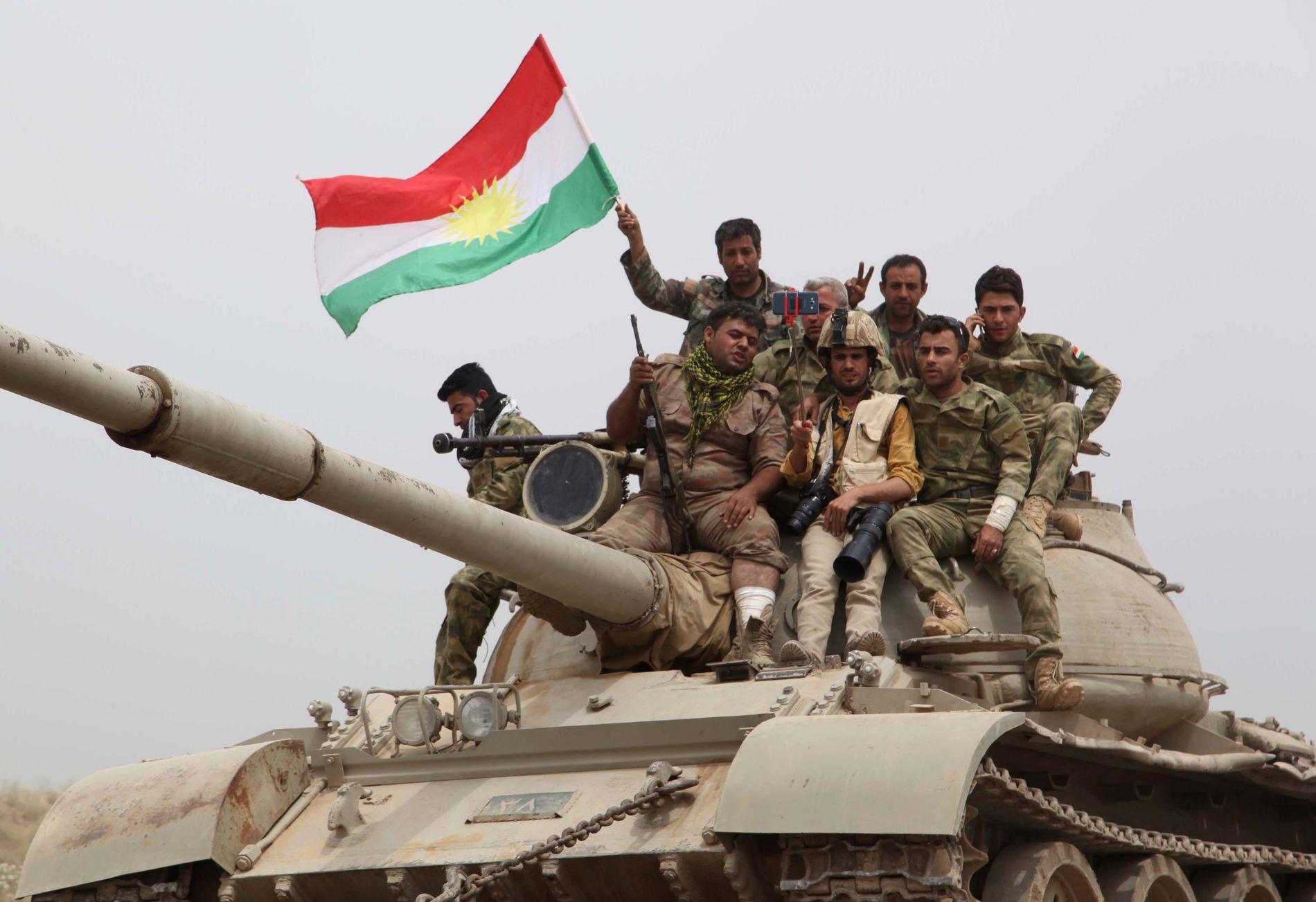 RYKKER FRAM: Kurdiske peshmerga-styrker vifter med det kurdiske flagget og tar selfie-bilder i det de ruller inn i den irkaske byen Bashir etter å ha fordrevet IS derfra i mai. Foto: AFP