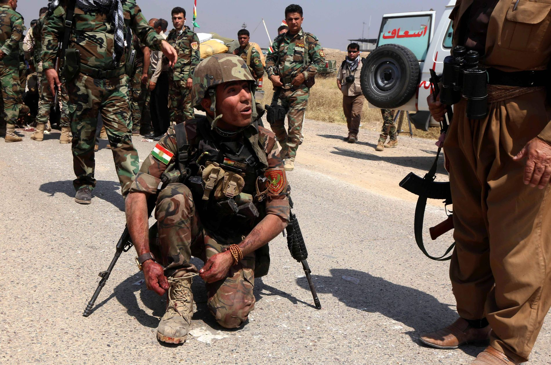 PÅ VEI MOT MOSUL: En kurdisk peshmerga-soldat knyter støvelen etter å ha inntatt en landsby 45 kilometer fra IS-bationen Mosul den 29. mai.