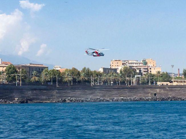 JAKTER SVAR: Et helikopter fra den italienske kystvakten saumfarer strandpromenaden ved havnen i Catania. Onsdag tar mannskapene opp igjen søket etter den savnede nordmannen.