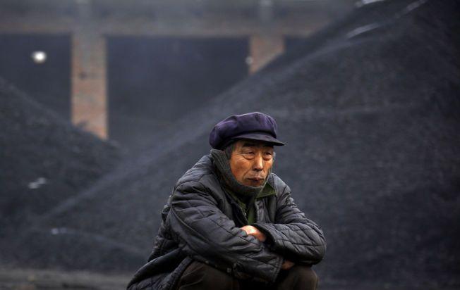 KINAS KULL: En eldre mann tar en pause fra å laste kull på biler ved byen Dangcheng.