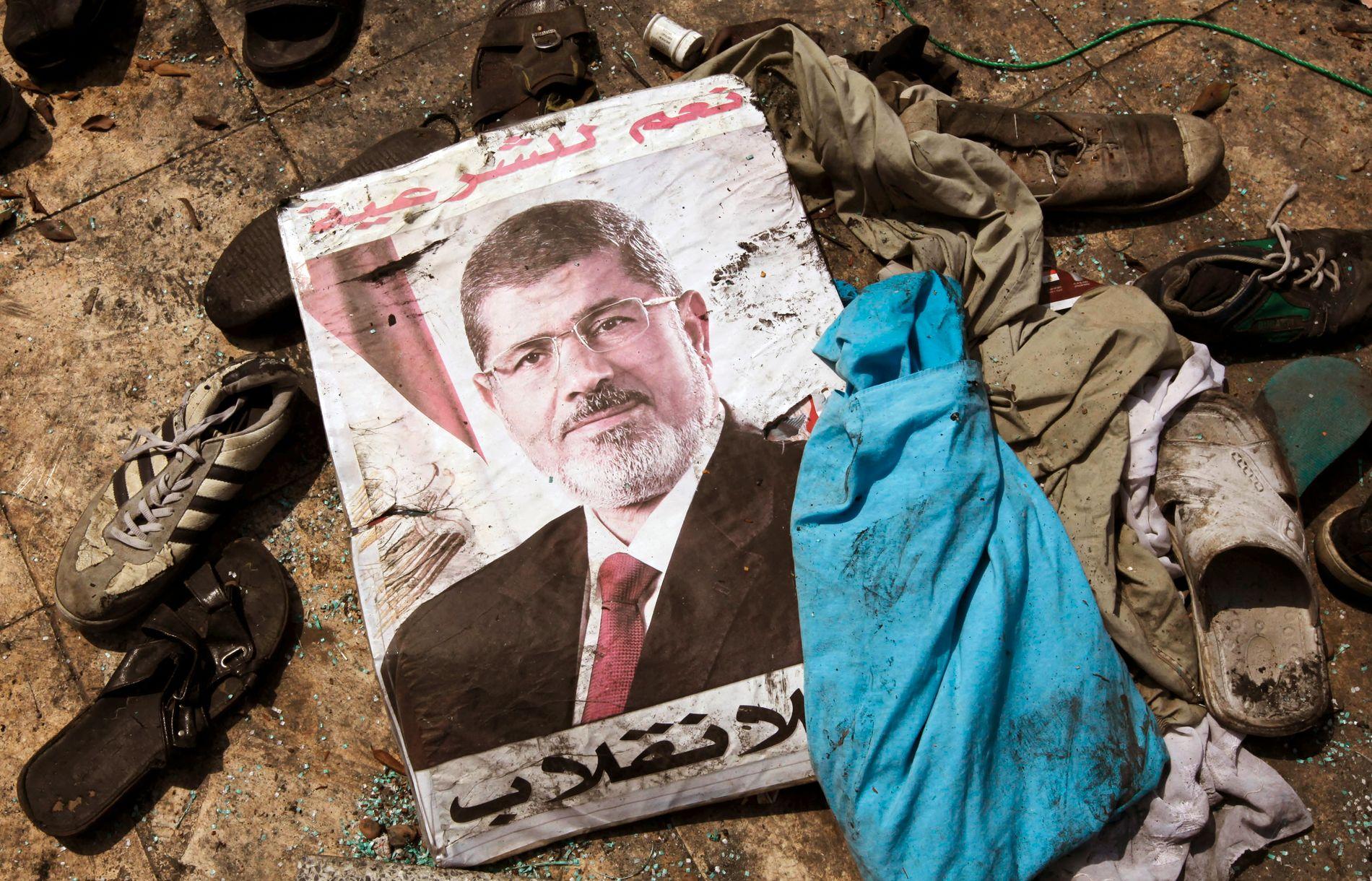 ETTER PROTESTEN: Et bilde av den avsatte presidenten Mohamed Morsi ligger sammen med rester fra demonstrasjonsleiren utenfor Rabaa moskeen i Kairo i august 2013.