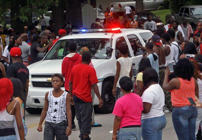 OPPRØR: Protesterende innbyggere i Ferguson, Missouri slår i siden på en politibil søndag kveld lokal tid. Innbyggerne var samlet for en minnestund for 18 år gamle Michael Brown, som skal ha blitt skutt og drept av en politimann lørdag. Ifølge nyhetsbyrået AP har politiet bekreftet at 18-åringen var ubevæpnet.