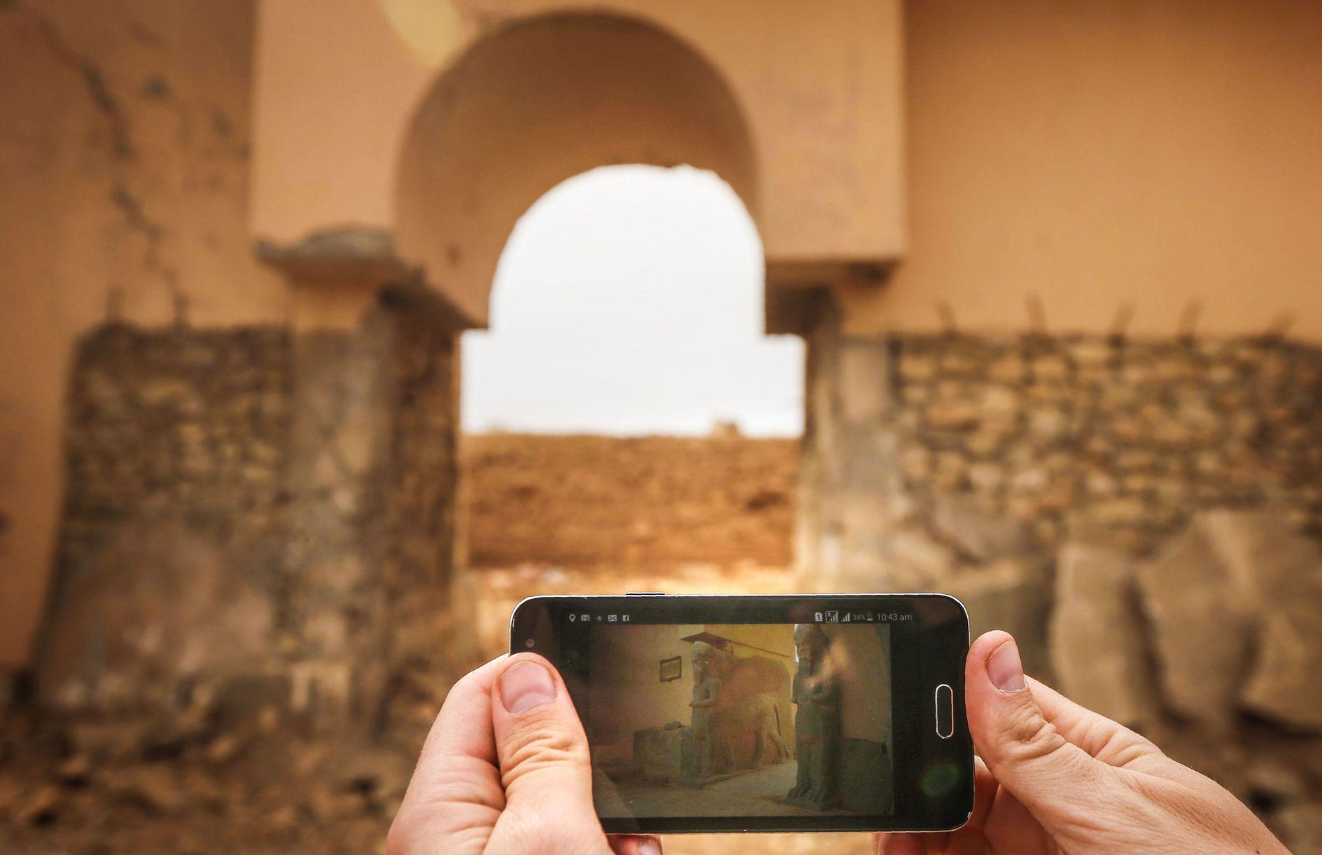HUGGET VEKK: Bildet er tatt i Nimrud denne uken. På telefonen vises et bilde av porthvelvingen slik den var: Med to kolossale statuer av bevingede okser.