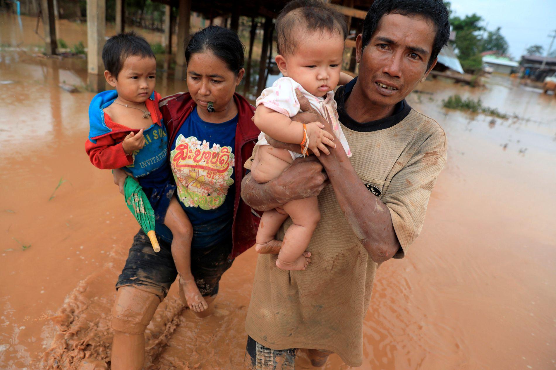 FLYKTER: Foreldre bærer sine barn på vei bort fra hjemmet etter oversvømmelsen etter dem-kollapsen i Laos.