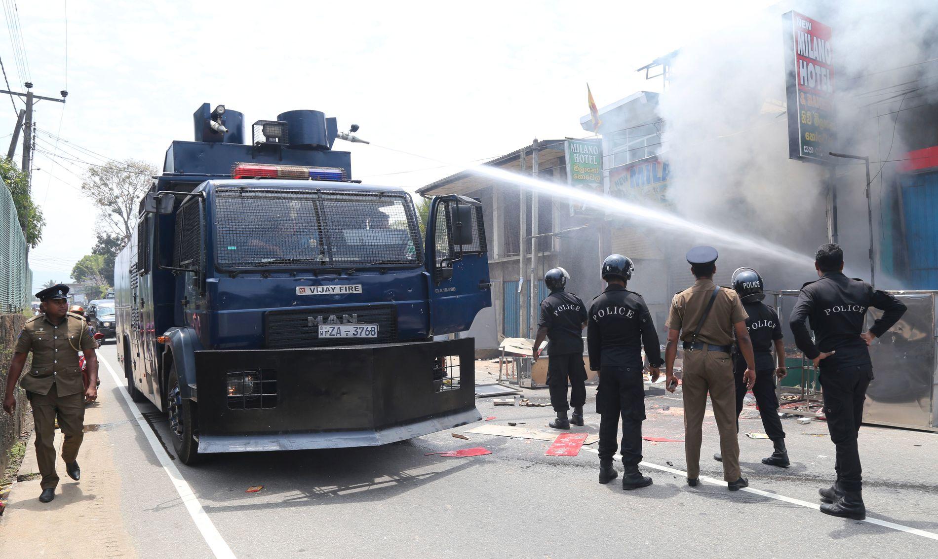 SLUKKER BRANN: Srilankisk politi ser på mens brannvesenet driver slukking av påtente butikker i Ambatenna på Sri Lanka.