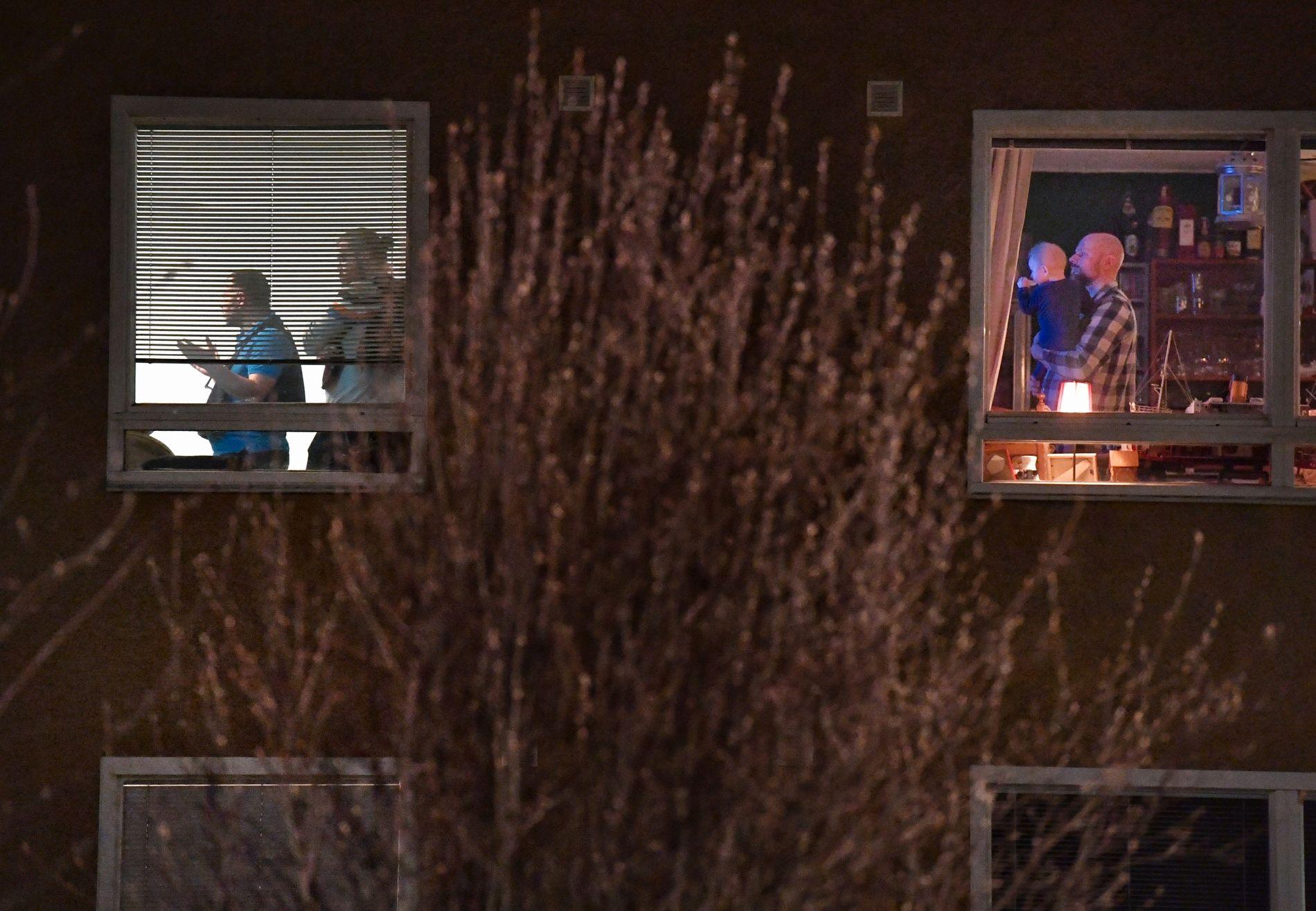 NÆR NABO: Patrick Behnke følger nyhetssendingene på TV med sønnen Erwin (10 md.) på armen mens bevæpnet politi gjennomsøker naboleiligheten. Foto: Helge Mikalsen