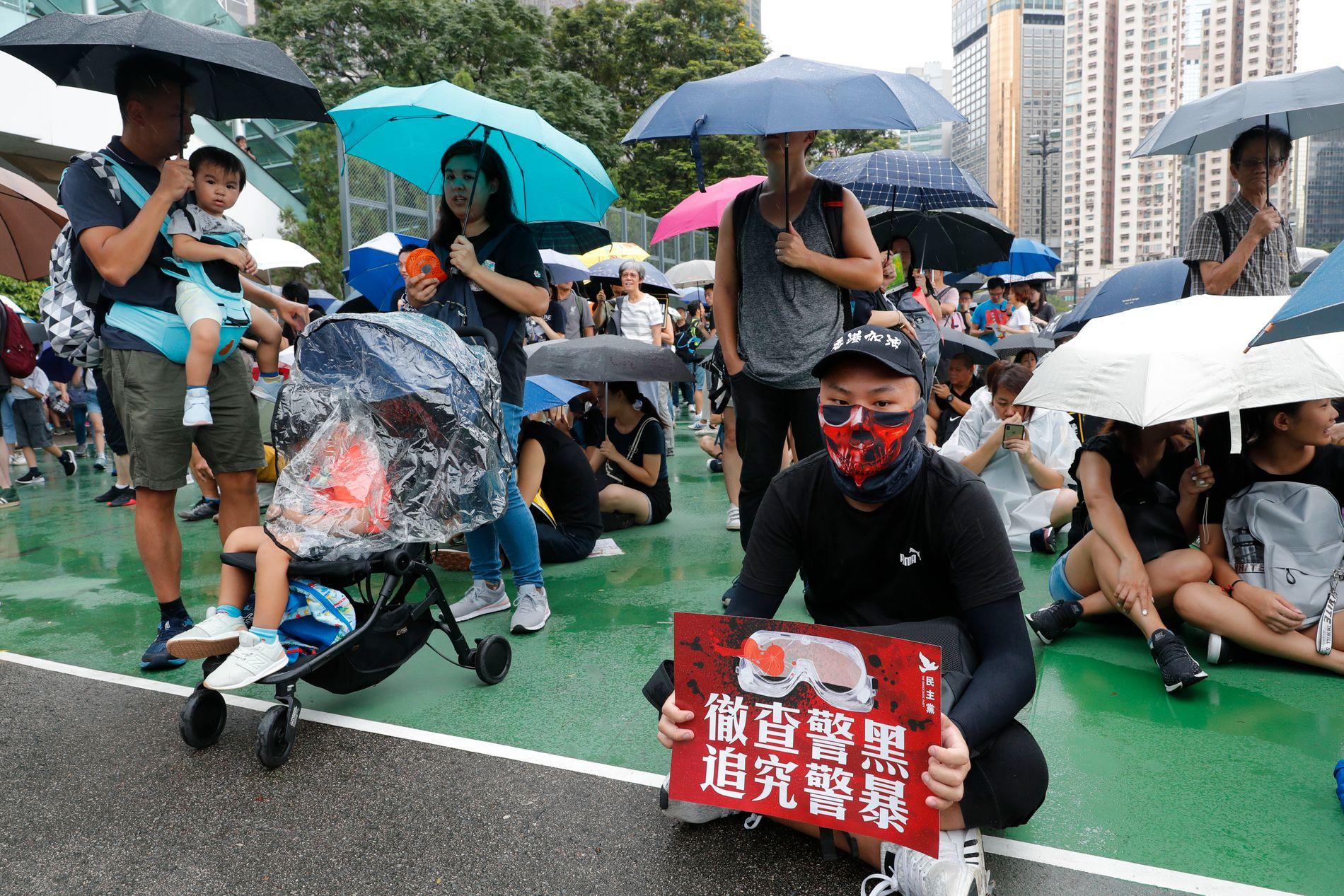 En av demonstrantene holder en plakat der det blir oppfordret til en grundig etterforskning av politivold og korrupsjon.