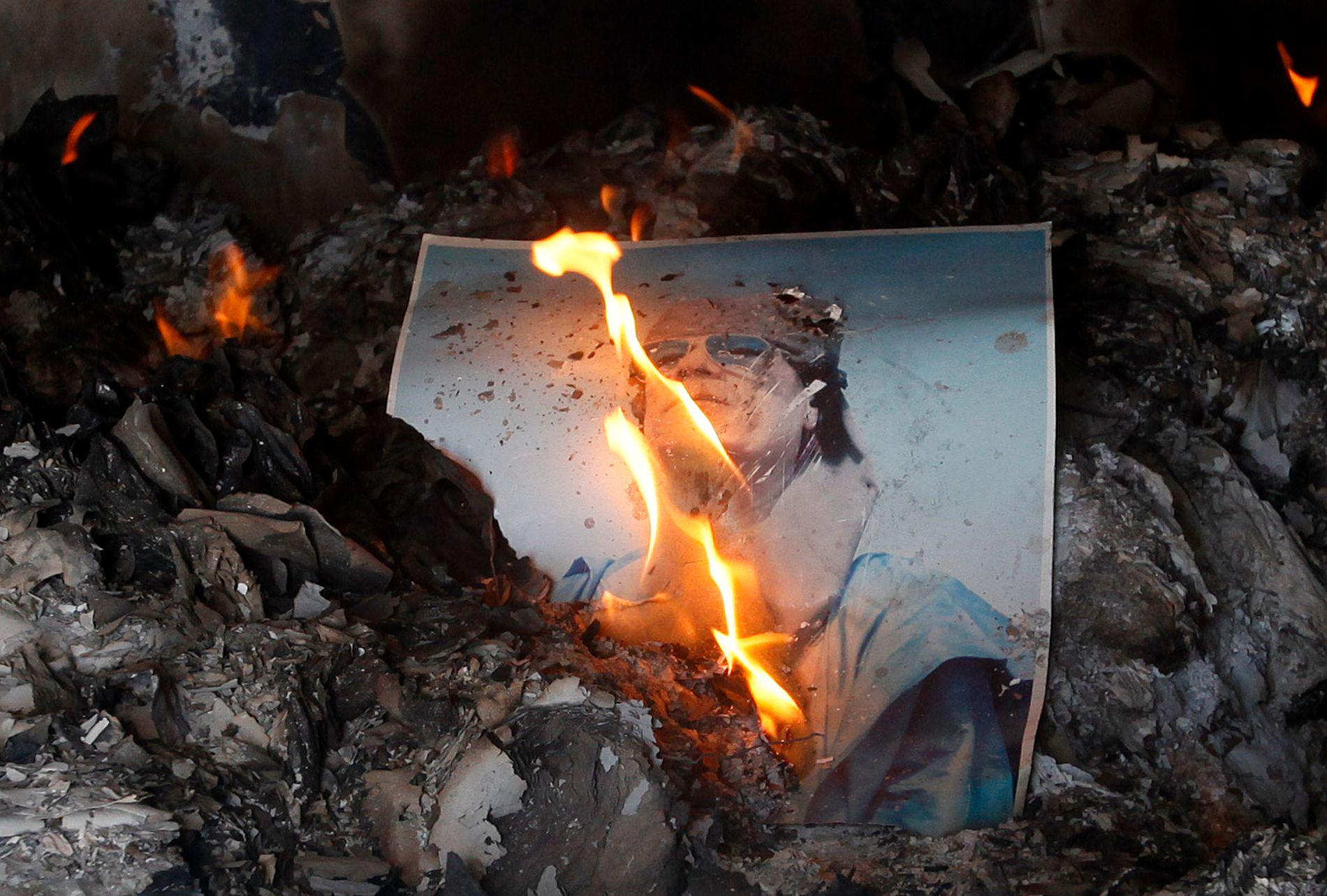 HER STARTET OPPRØRET: Et brennende bilde av Muammar al-Gaddafi, inne i et av hans fengsler i Benghazi, februar 2011, få dager etter at opprøret startet i byen.