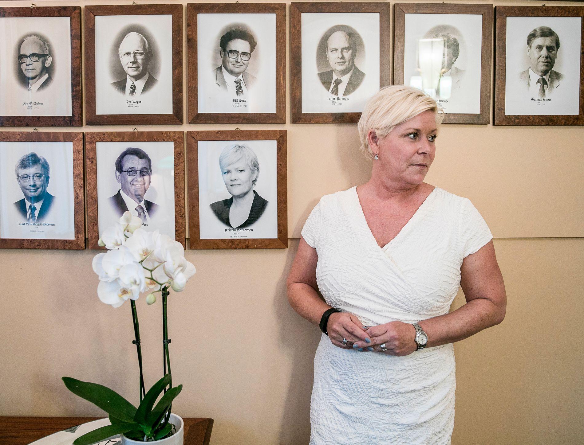SAMARBEIDSVILLIG: Finansminister Siv Jensen (Frp) foran veggen hvor bilder av tidligere finansministere har fått plass.