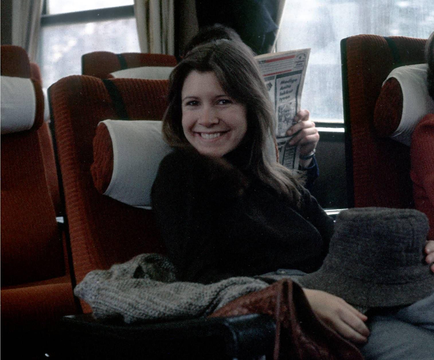 HATTEGLAD: Carrie Fisher på toget til Finse, kanskje med en hatt hun plukket opp i Oslo.