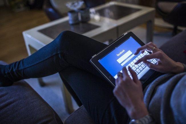 SOSIALE FELLER: En kvinne logger seg på Facebook på nettbrettet sitt hjemme i sofaen. Ikke alle er like obs på hva de deler av opplysninger på sosiale medier.