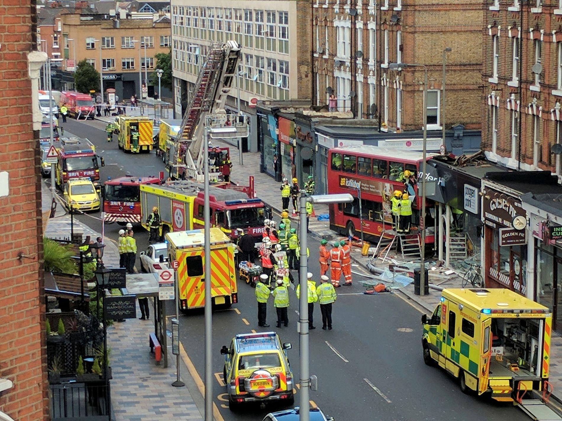 KRASJET INN I BUTIKK: Britiske nødetater er på stedet der bussen smalt inn i Poggen Pohl Kitchen Design Centre i Lavender Hill, i London.