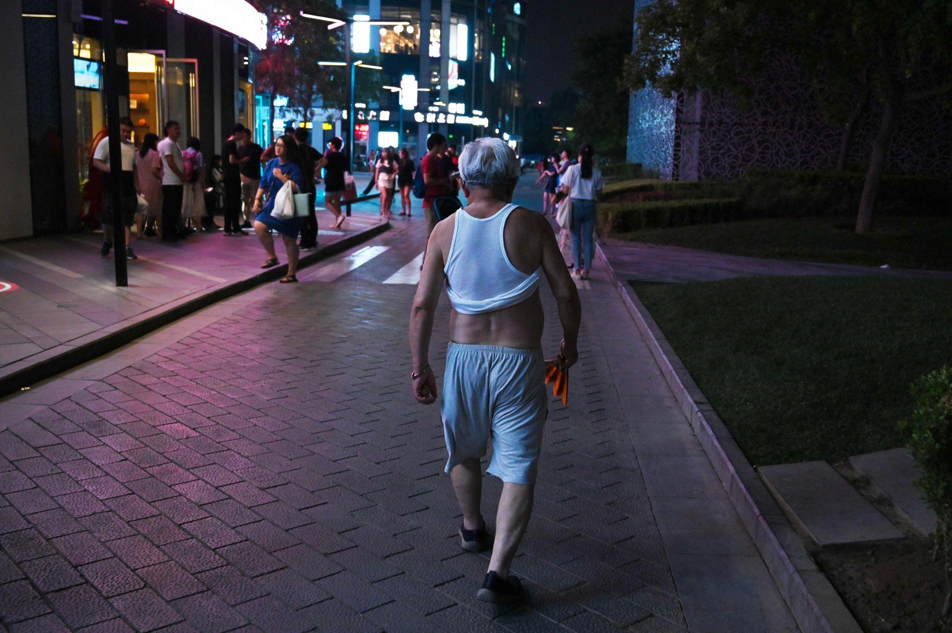 HETT: En mann går med trøyen rullet opp over magen utenfor et kjøpesenter i Beijing 28. juni i år.