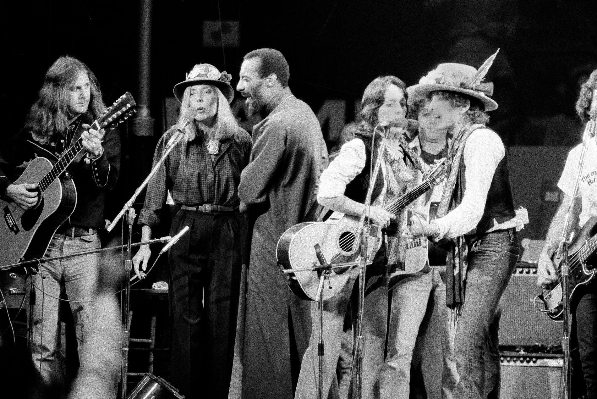 LEGENDARISK: Musikerne Roger McGuinn, Joni Mitchell, Richie Havens, Joan Baez og Bob Dylan under finalen av «The Rolling Thunder Revue»-turneen i desember 1975.