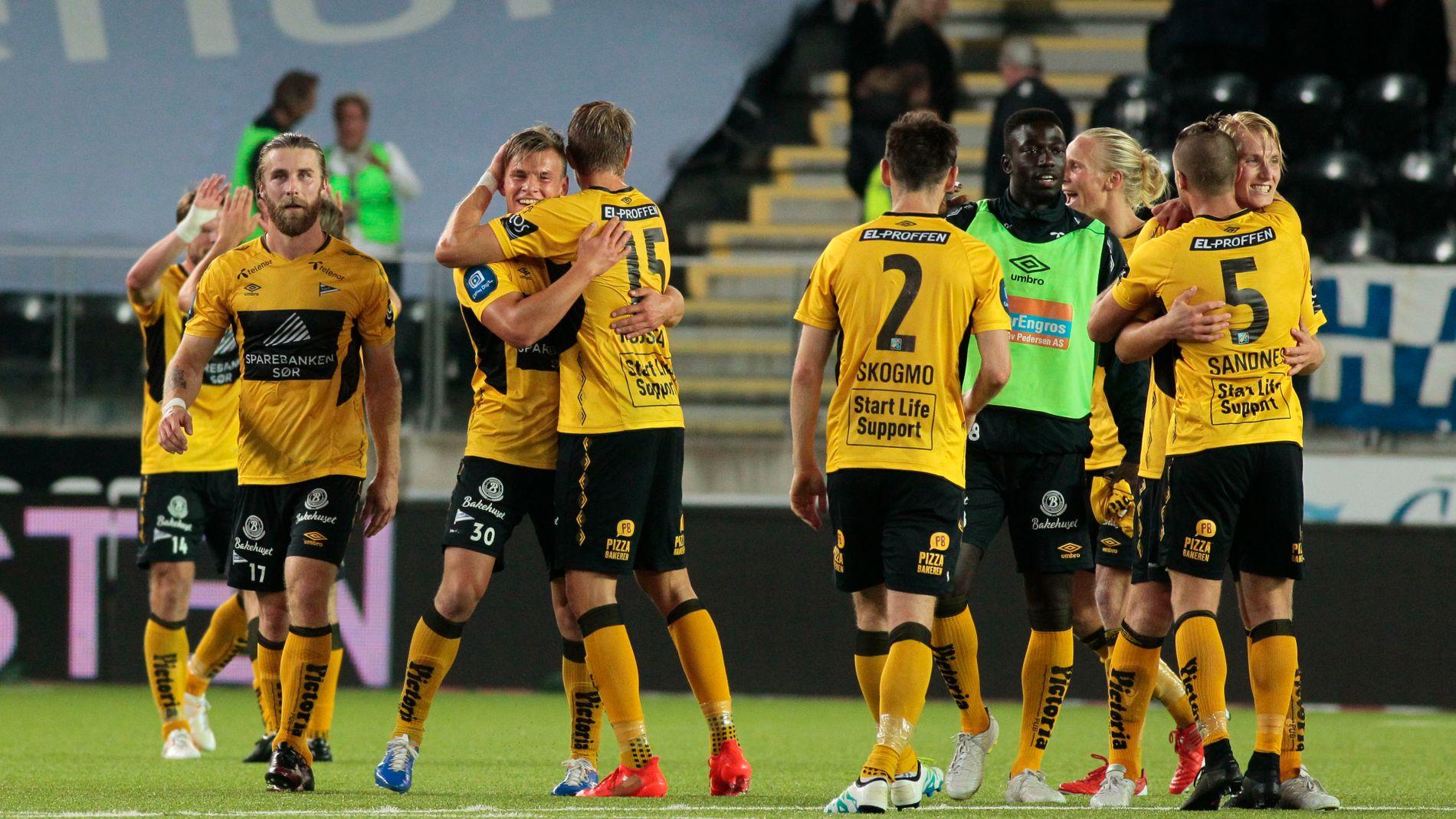 ELLEVILL JUBEL: Start-spillerne omfavner Lasse Sigurdsen (nummer tre fra venstre med draktnummer 30) etter at 19-åringen sikret sørlendingenes første seier på evigheter i fotballverdenen.