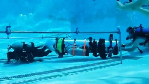 TESTER: Simulering av manøvrering gjennom en trang passasje, skriver Elon Musk under videoen av to dykkere som frakter det lille ubåtfartøyet i et basseng.