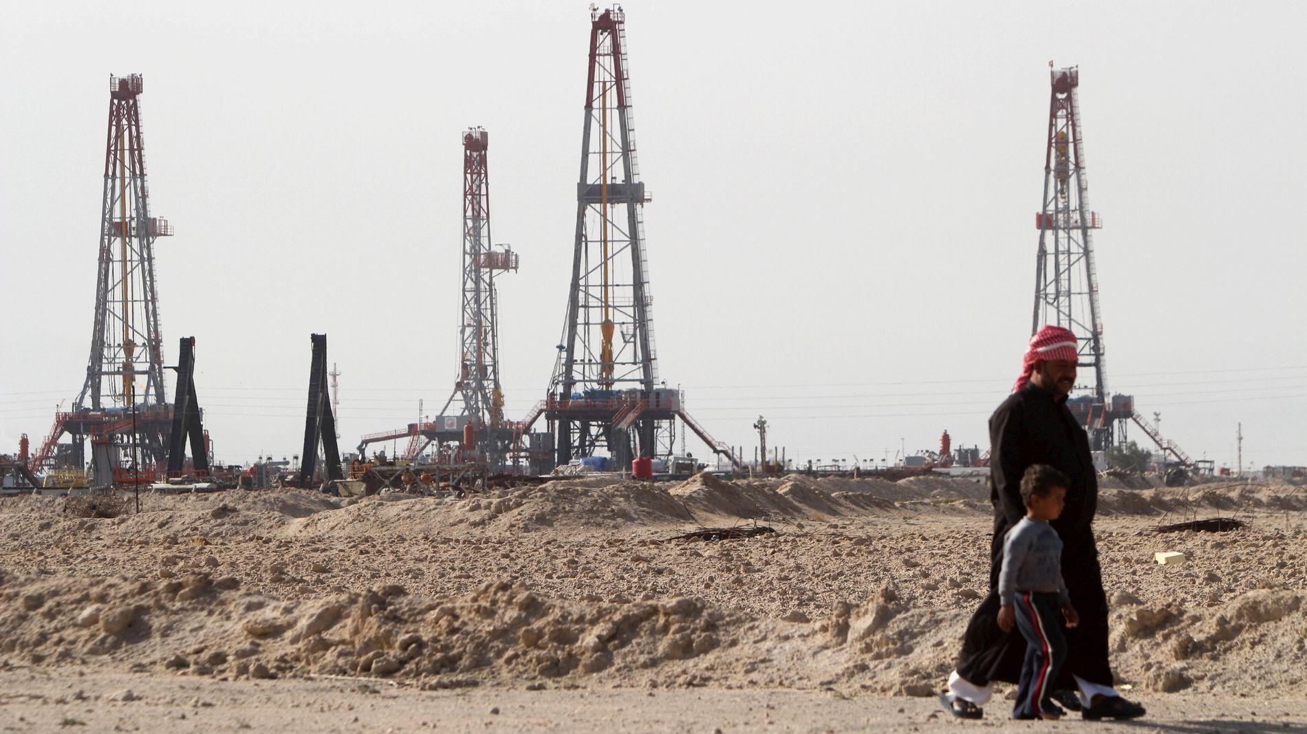 HVA GJØR OPEC? Klarer de å få kuttet produksjonen effektivt, og få opp oljeprisen? Her ser vi far og sønn spassere forbi Rumaila-oljefeltet i Basra i Irak.