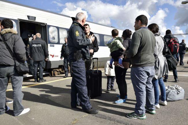 I DANMARK: Syriske flyktninger snakker med en politimann etter å ha ankommet Rødby i Danmark.