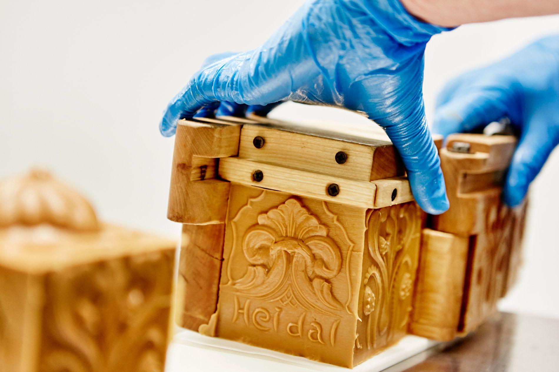 HISTORISK BRUNOST: En ferdig stappet Heidalsost med akantusmønster tas ut av formen. Dette er tradisjonelle osteformer laget av en lokal treskjærer.