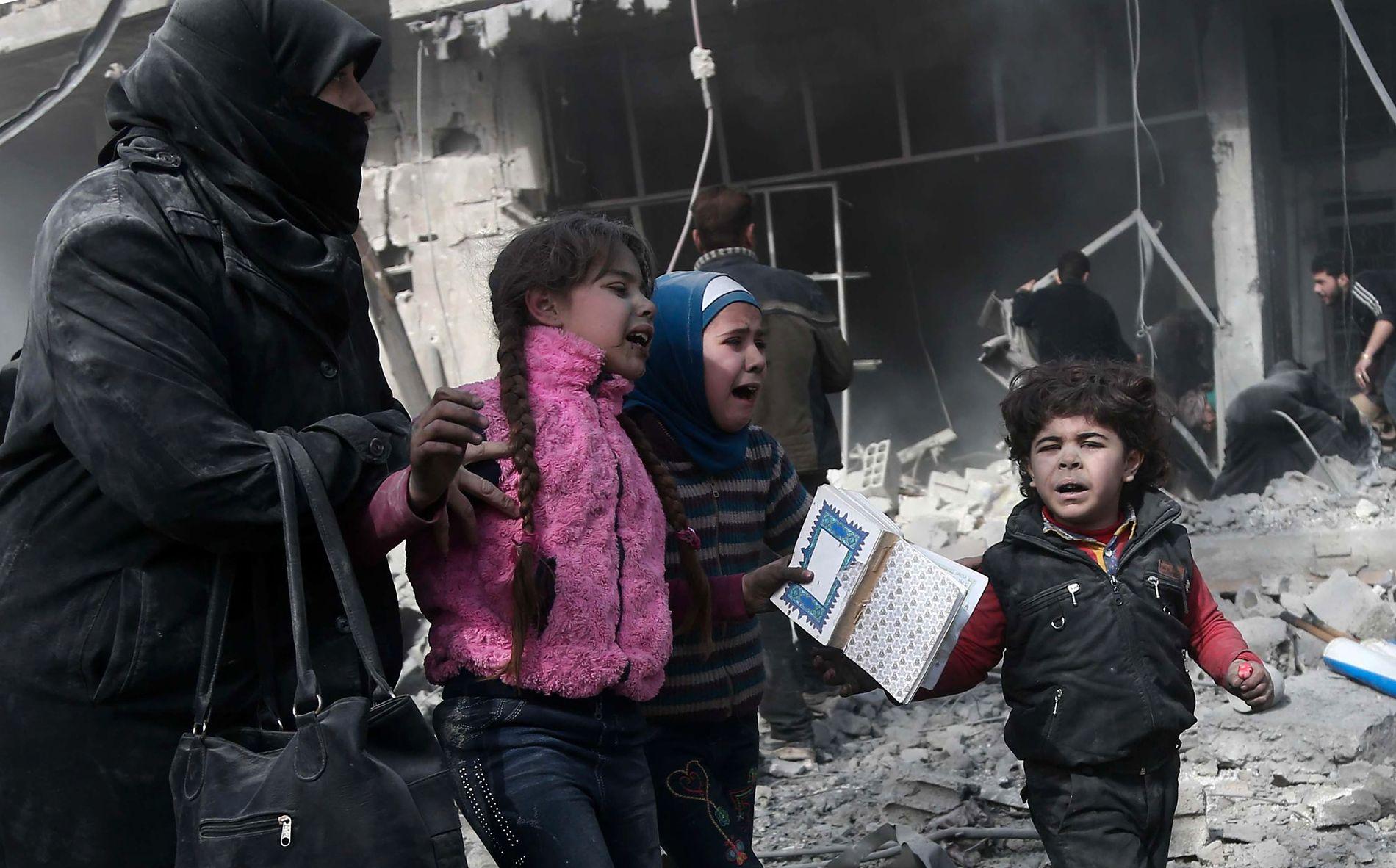 REDDET: Barn hjelpes ut av en bombet bygning i Harmouria i Øst-Ghouta mandag.