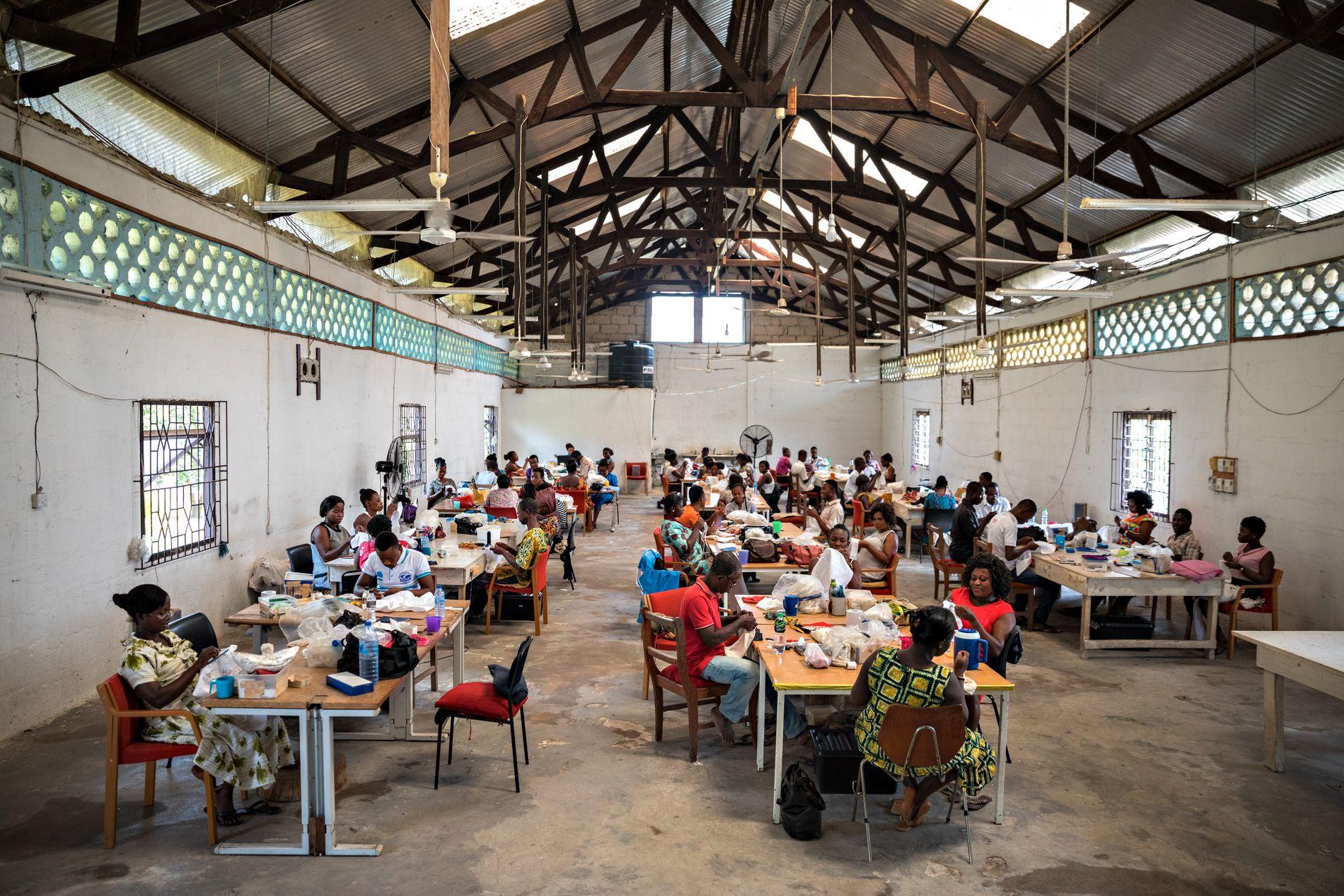 MASSEPRODUKSJON: Dette er en norsk bunadssystue i Kumasi, Ghana. Her holder 70 ghanesere norsk håndverkstradisjon ved hevd. Vinduene i bygningen kommer fra et borettslag i Hordaland, og den store vifta på veggen er fra det gamle trykkeriet til avisen Bergens Tidende.