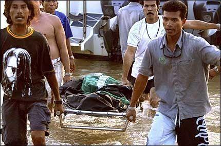OMKOMMET: Redningsarbeidere bærer en omkommet inn på land i Krabi. Foto: EPA