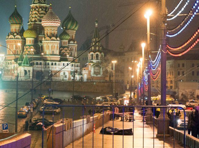 DREPT PÅ ÅPEN GATE: Nemtsovs kropp, dekket av svart plast, ligger på Moskovorestky-broen nær St. Basil-katedralen sentralt i Moskva.