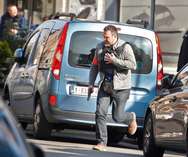 AKSJONERER MOT TERRORMISTENKTE: Her er en bevæpnet politimann avbildet løpende over gaten i Rue de Dries tirsdag ettermiddag, like ved stedet der tre kolleger ble såret under en aksjon mot en leilighet i den belgiske hovedstaden.