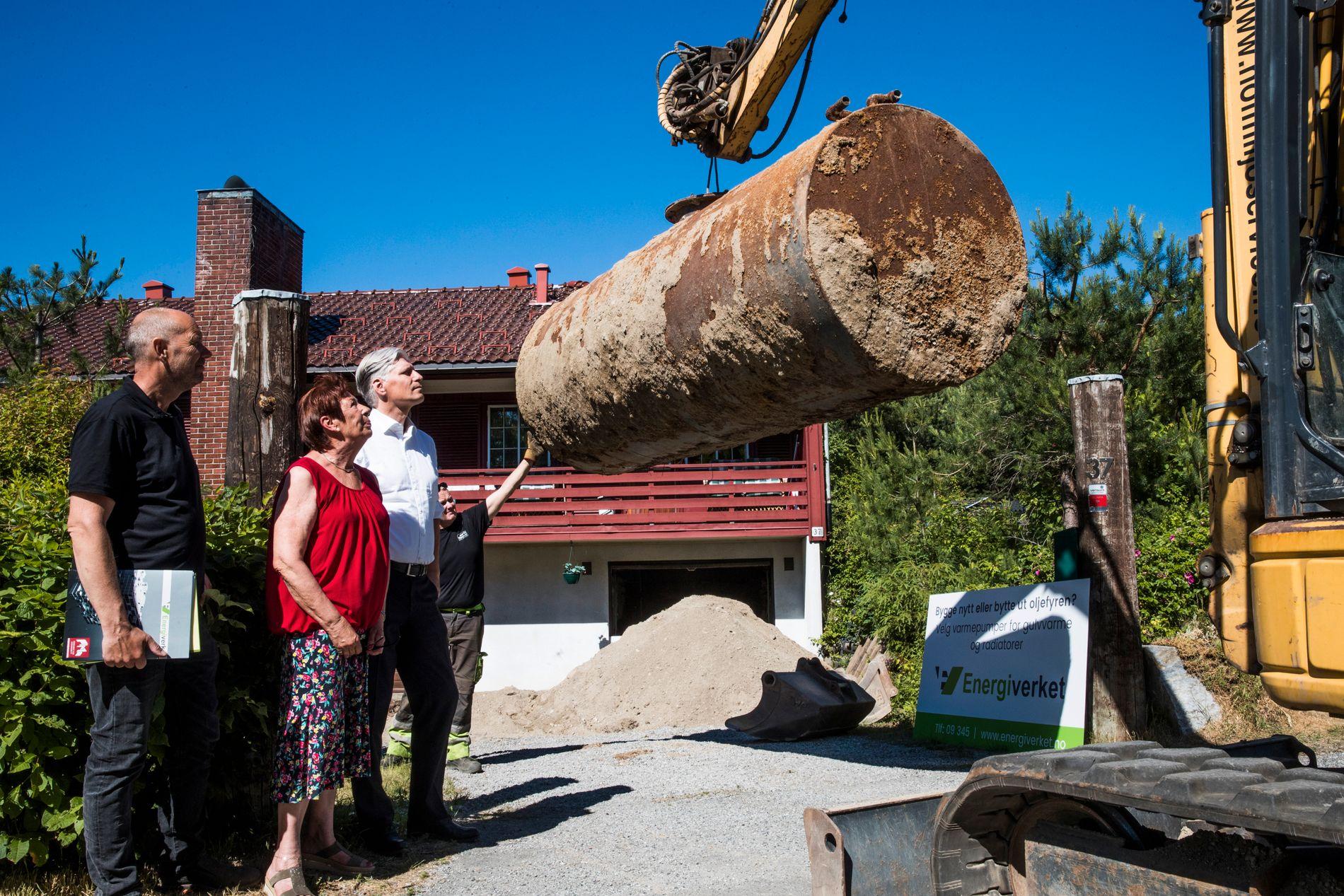 TANK TIL BESVÆR: Anita Loe er veldig glad for å få fjernet oljetanken som har ligget under bakken siden 1948. Her sammen med svigersønnen, Vidar Jensen (t.v.) og klima- og miljøminister Ola Elvestuen.