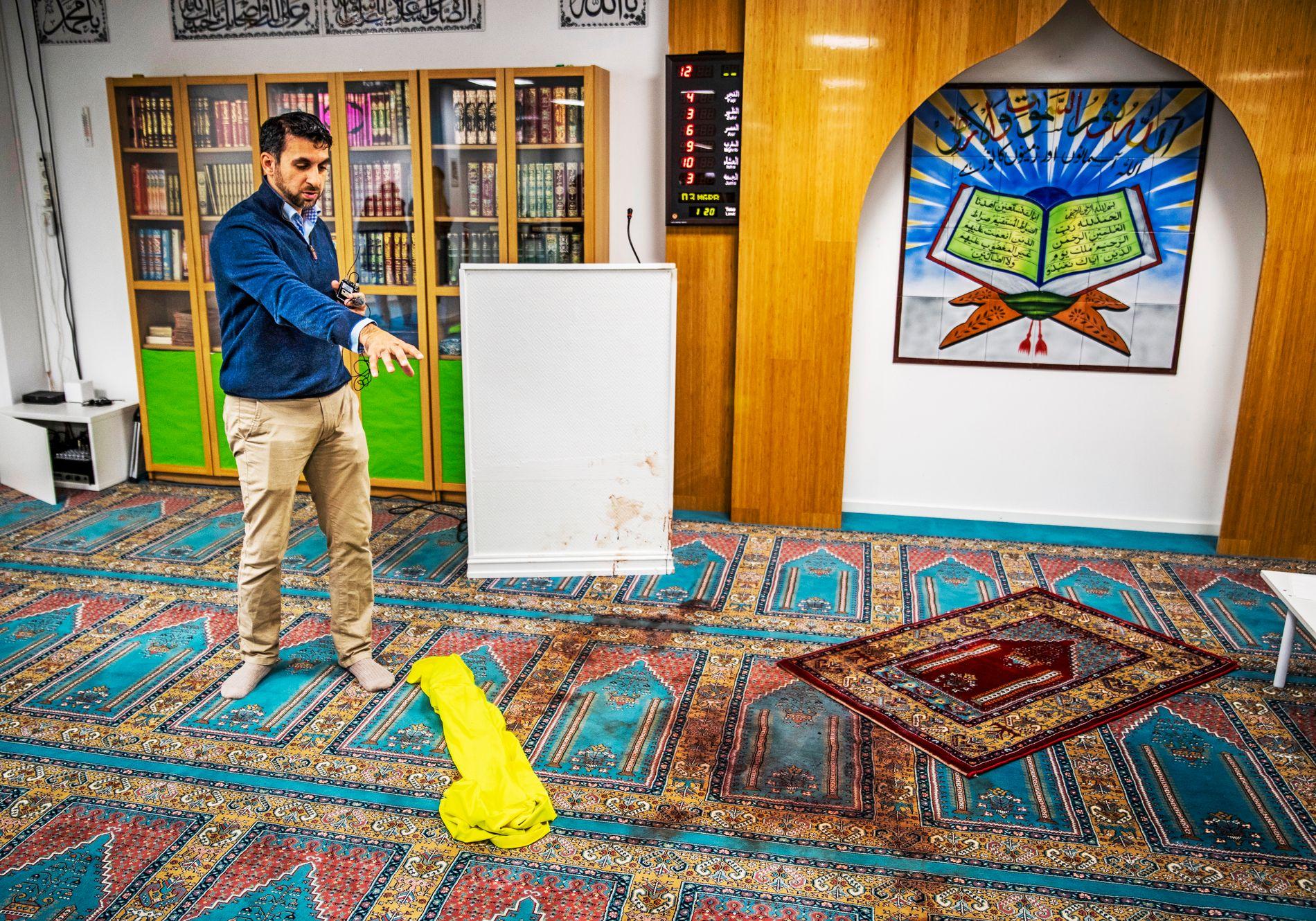 ÅSTEDET: Angrepet mot Al-Noor-moskeen i Bærum sist lørdag har satt tydelig spor i bønnerommet. Styremedlem Irfan Mushtaq har i dag åpnet dørene for pressen og peker mot stedet hvor terrorsiktede Philip Manshaus (21) sloss med et medlem i moskeen.