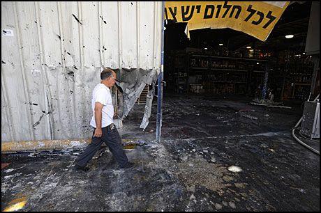 NEDSLAGSSTED: En mann går forbi stedet der en rakett, avfyrt fra Gazastripen, slo ned i en fabrikk i kibbutzen Nir Oz torsdag og tok livet av en mann. Foto: REUTERS