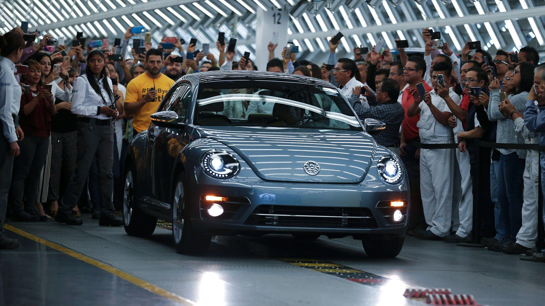 DEN SISTE! Arbeiderne ved bilfabrikken i Puebla i Mexico tar bilde når den siste produserte Beetle-bilen ruller for første gang