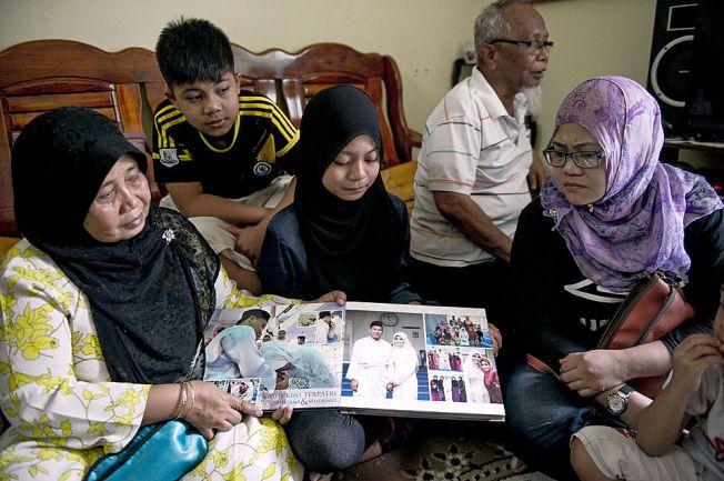 BARE MINNENE IGJEN: Familien til det savnede ekteparet ser på bryllupsbildene. De fortviler over manglende svar om hva som har skjedd med MH370. Foto: AFP/ NTB Scanpix