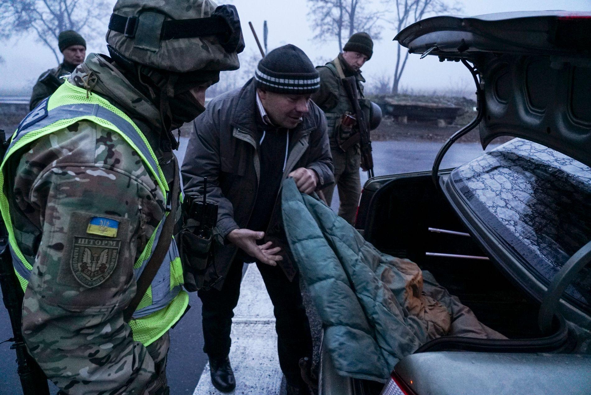 STOPPER BILER: Soldater og en politimann søker i en bil nær kontrollpunktet nær den ukrainske byen Mariupol tirsdag.
