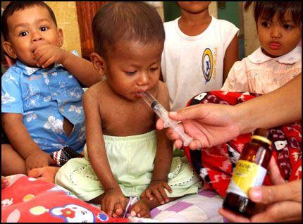 SMITTET: Bun Leap får medisin på et helsesenter i Kambodsja. Hiv-smitte mellom mor og barn er svært utbredt i Asia og Afrika. Foto: EPA.