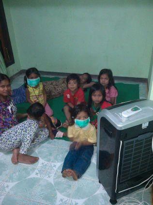 SLIPPER IKKE UNNA: Åtte indonesere forsøker å skjerme seg fra den farlige røyken, som nå trenger seg inn i hus.