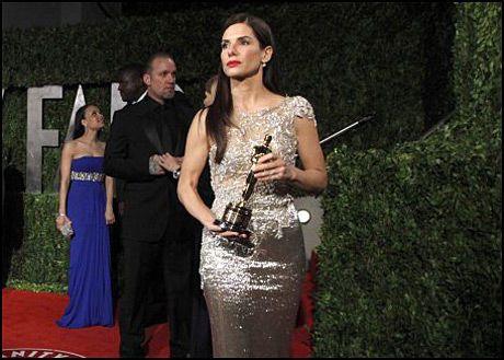 KRISE: Sandra Bullock med Oscar-statuetten 7. mars. I bakgrunnen står ektemannen Jesse James, som ti dager senere ble avslørt i utroskap. Foto: AP