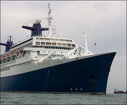 TRIST SKUE: Som «Blue Lady» har SS «Norway» den siste måneden ligget i opplag utenfor kysten av India. Nå slepes den opp på stranden for opphugging. Foto: AFP Foto: AP