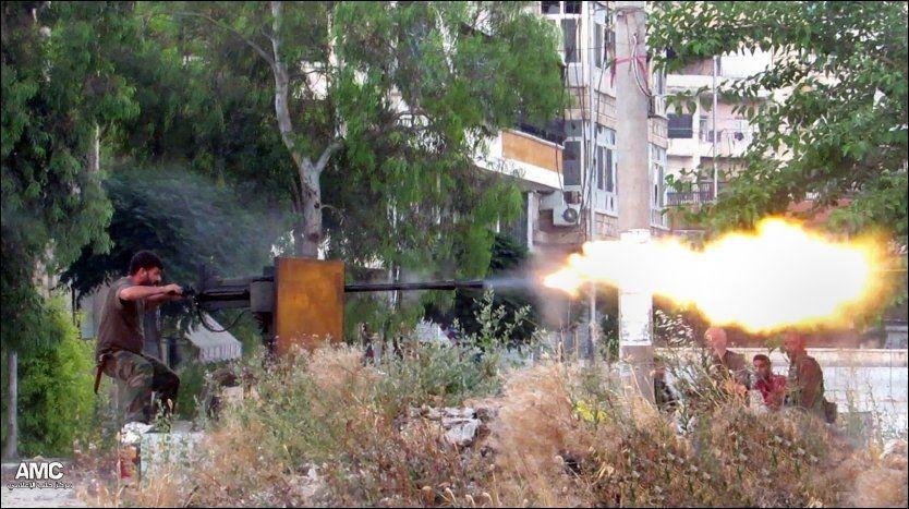 TUNGTRENING: Syriske opprørere har mottat trening i bruk av tungt militært materiell fra USA. Bildet viser en opprører som avfyrer et maskingevær i kamper i Aleppo torsdag. Foto: AP, NTB SCANPIX