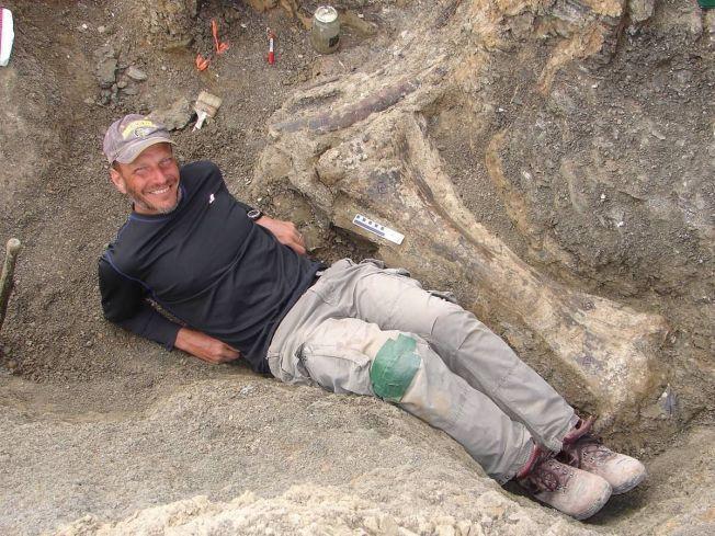 LEGGEN: Leder av utgravningene, Kenneth Lacovara, har lagt seg ved siden av leggbeinet til dinosauren.