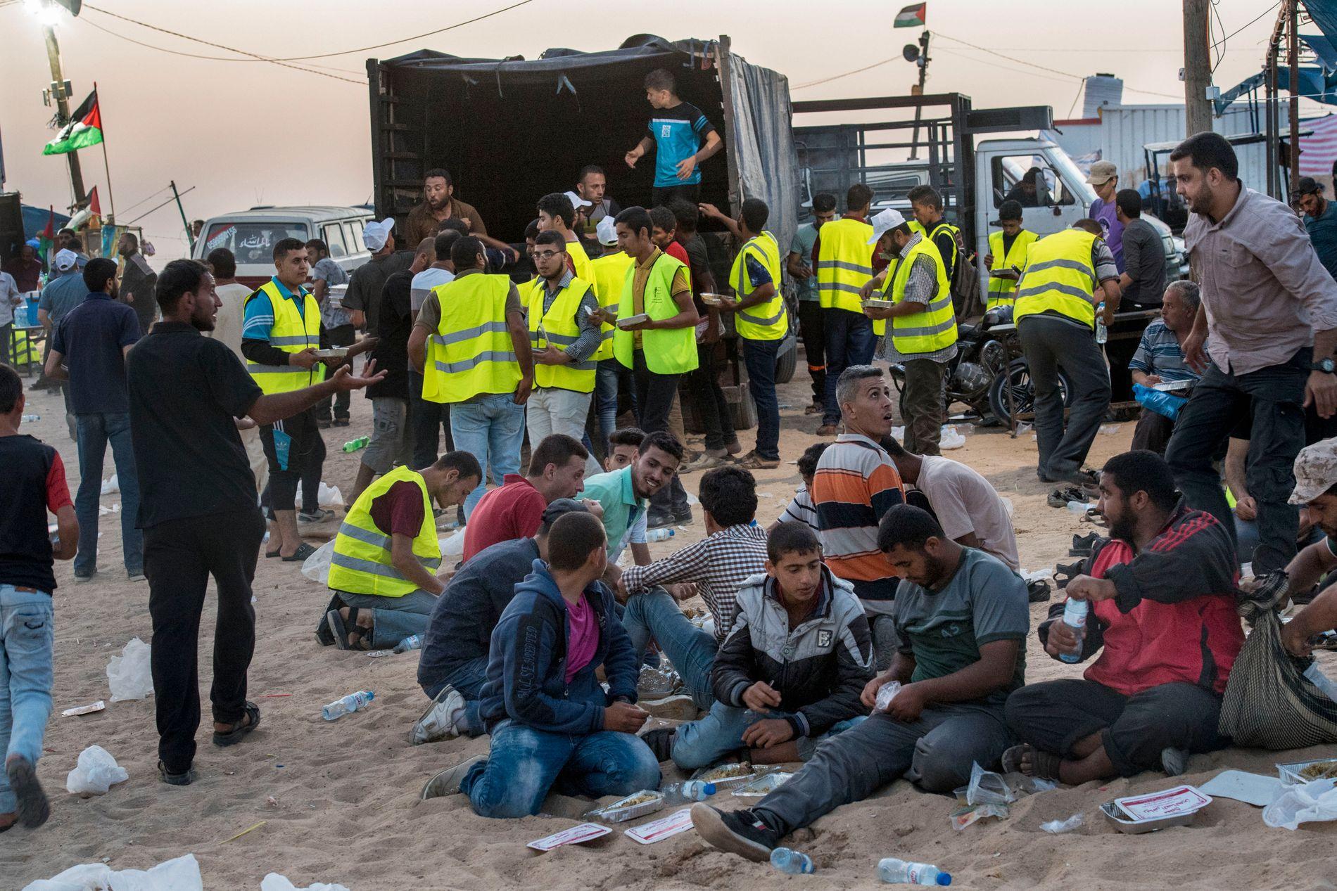 MATKAOS: Noen nærmest sloss om maten som Hamas-medlemmer delte ut til demonstrantene. Forretten besto av tre dadler og og hovedretten var ris og kjøtt.