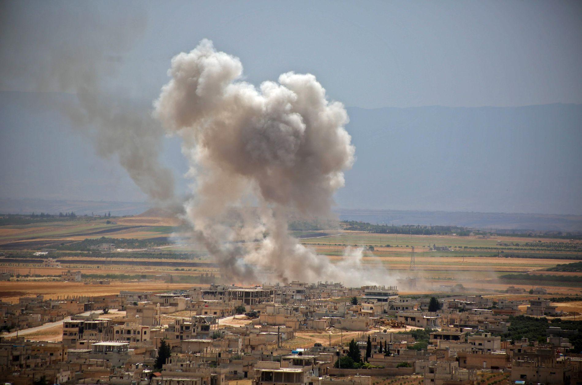 BOMBES: Røyk stiger opp etter en angrep i Khan Sheikhun, sør i Idlib i juni.