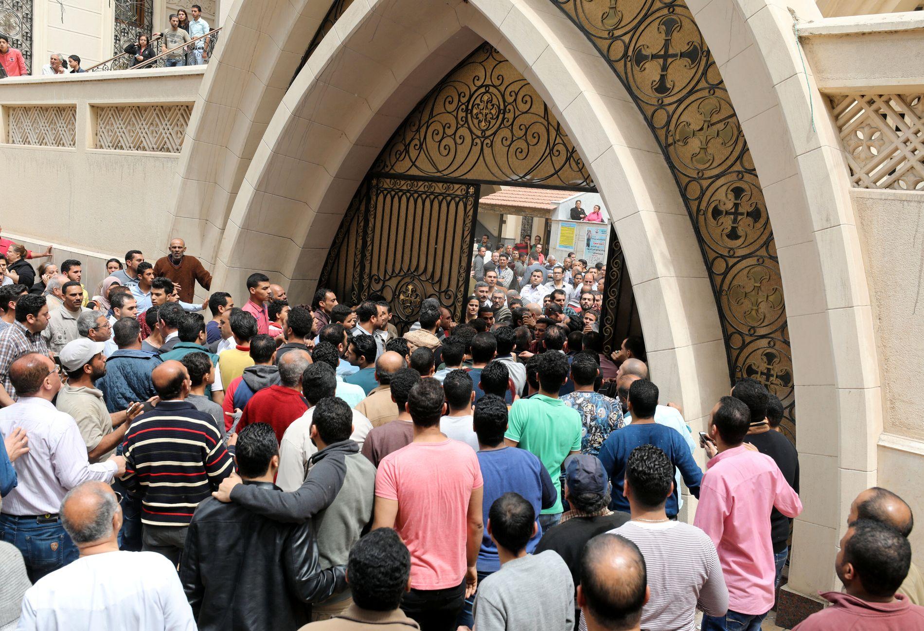 ANGREPET: Tilskuere og etterlatte samler seg utenfor en av kirkene som ble rammet av bomber i Egypt søndag.
