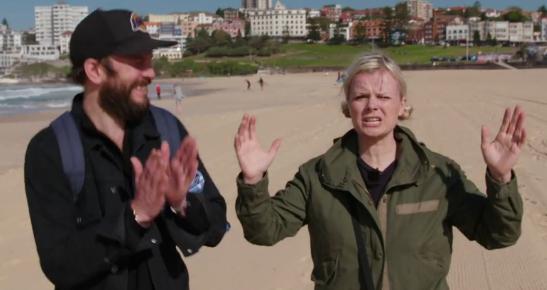 PÅ STRANDA: I episode 2 av reiseprogrammet «Jorden rundt på seks steg» befinner programlederne Kåre Magnus Bergh og Ingrid Gjessing Linhave seg på Bondi Beach i Sydney, hvor de snakker med surfere.