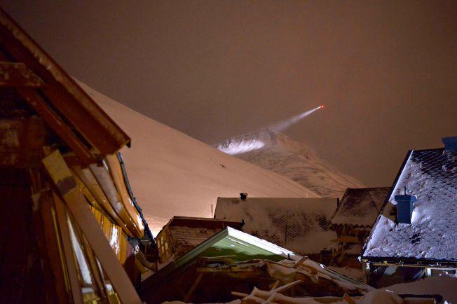 Helikoptre jobber med søkelys i mørket, for å undersøke om området der snøraset gikk lørdag, fremdeles er rasutsatt.