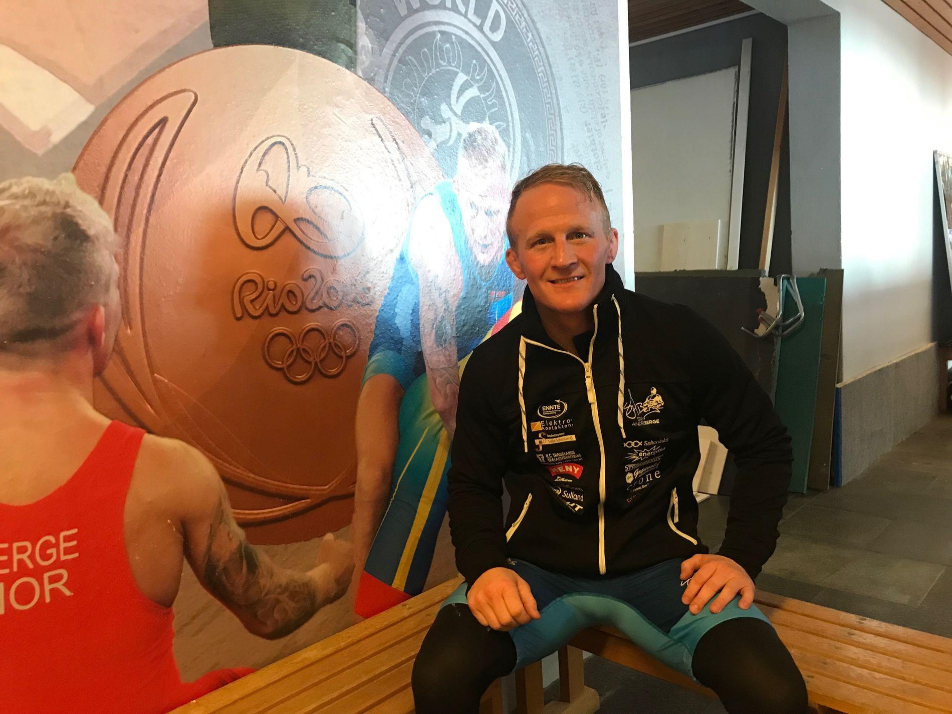 VEGGPRYD: Stig-André Berge (35) må komme blant de seks beste i 60-kilosklassen i VM i Astana i september for å kvalifisere seg til sitt fjerde OL. Her sitter han foran bilder av seg selv som pryder en vegg i treningslokalet på Kalbakken i Oslo.